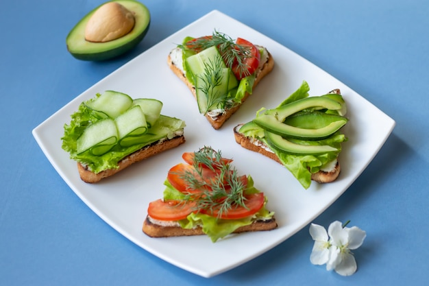 Vegetarian sandwiches with avocado, tomatoes and cucumbers on a blue background