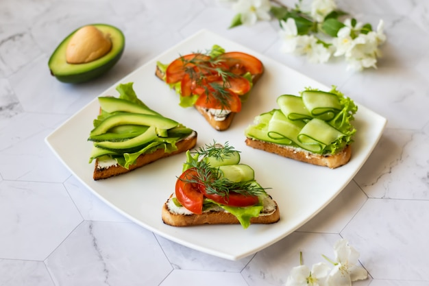 Vegetarian sandwiches with avocado, tomatoes and cucumbers on a light background