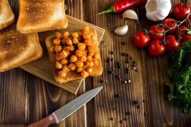 Вегетарианские бутерброды с нутом в томатном соусе и ингредиентами на деревянных фоне. вид сверху.