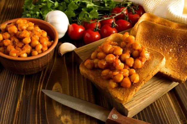 Вегетарианские бутерброды с нутом в томатном соусе на деревянной разделочной доске