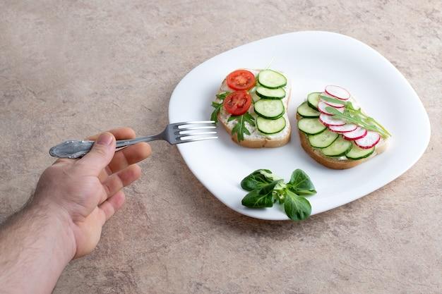 Вегетарианские бутерброды с творогом, огурцами, помидорами и редисом на белой тарелке. рука держит вилку над белой тарелкой с бутербродами.