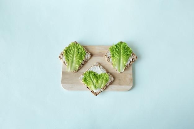 クリスプブレッド、グリーンサラダ、ソフトチーズフラットのベジタリアンサンドイッチが明るい背景に置かれています。ミニマリズムのコンセプト