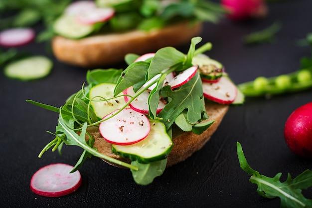 Vegetarian sandwiches with cucumber, radish, arugula and green peas