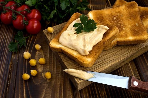 木製のまな板にフムスとベジタリアンサンドイッチ