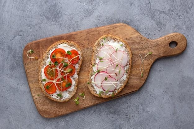Вегетарианские бутерброды с овощами, микро зеленью и зерновой хлеб на бетонном фоне