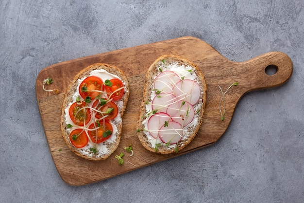 Vegetarian sandwiches with vegetables, microgreens and grain bread on a concrete background