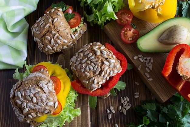 木製のテーブルに野菜とベジタリアンサンドイッチ。上面図。