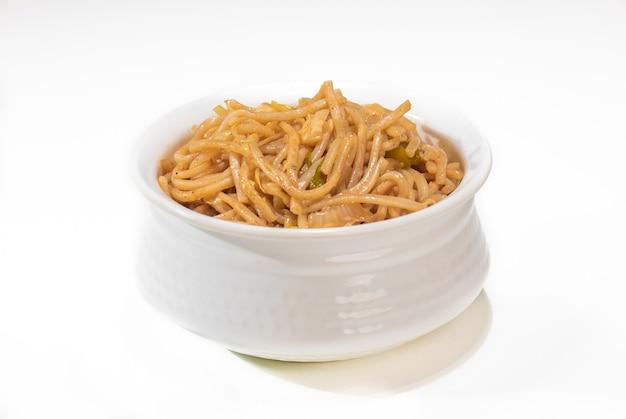 暗い背景の黒いボウルにベジタリアンシェズワンヌードルまたは野菜ハッカヌードルまたは焼きそば。 schezwan noodlesは、うどん、野菜、チリソースを使ったインド風中華料理の温かい料理です。