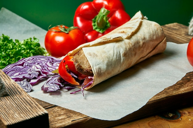 Vegetarian shawarma roll in pita with lettuce, vegetables, and soy meat. tasty, wholesome and green food. vegan street food
