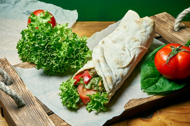 Vegetarian shawarma roll in pita with lettuce, vegetables, and tomato. tasty, wholesome and green food. vegan street food