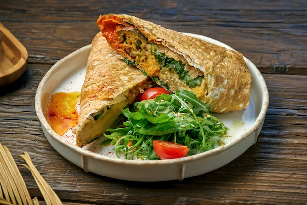 Vegetarian shawarma roll with spinach, tomatoes, hummus and melted cheese in a plate on a wooden table