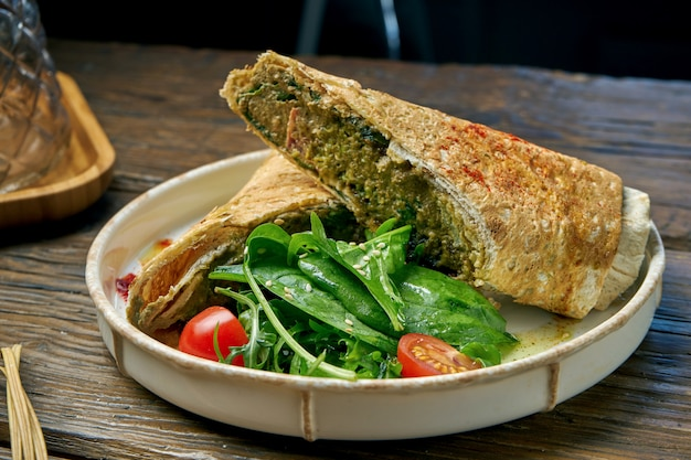 Vegetarian shawarma roll with spinach, tomatoes, hummus and melted cheese in a plate on a wooden
