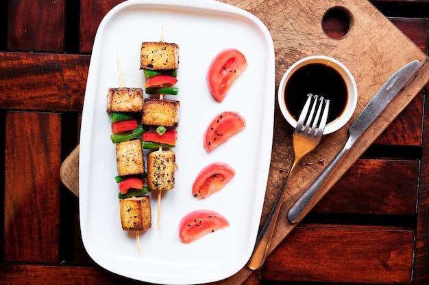 トマトと白いプレートに明るいソースと野菜の串焼き