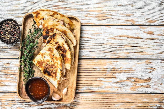 木製トレイに野菜とチーズを添えたベジタリアンスナックケサディーヤ。白い木製の背景。上面図。スペースをコピーします。