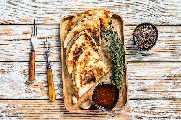 木製トレイに野菜とチーズを添えたベジタリアンスナックケサディーヤ。白い木製の背景。上面図。