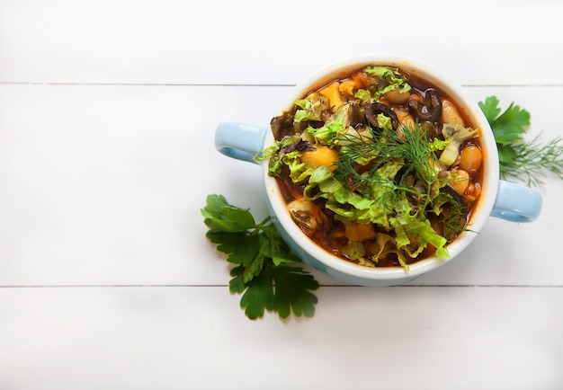 Вегетарианский суп с фасолью и свежей петрушкой в керамической миске на белом деревянном столе. вегетарианская пища.