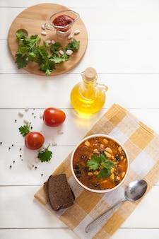 セラミックカップに豆とオリーブとトマトを入れた野菜スープ、白い木製のテーブルに黄色いリネンナプキンにオリーブオイル。フラットレイ。