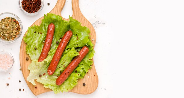 Vegetarian spiced sausages on lettuce leaves. white background. copy space. banner