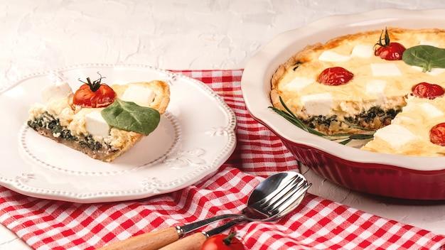 菜食主義のほうれん草のパイまたは明るい背景にフェタチーズのタルト