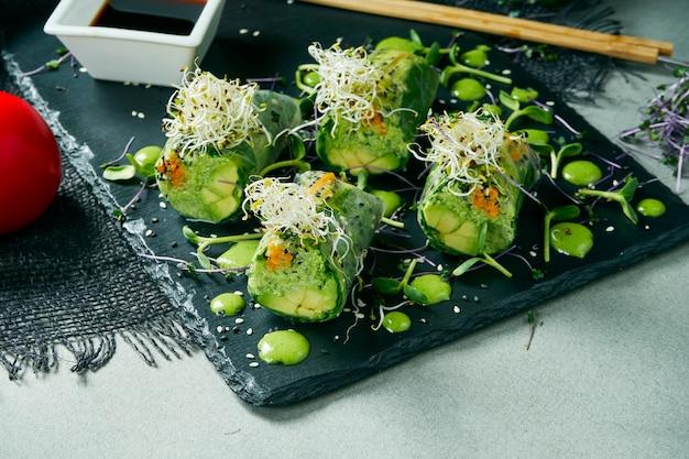 Вегетарианский блинчик с начинкой с авокадоом в рисовой бумаге на черной доске шифера. серый стол. здоровая диета. закрыть