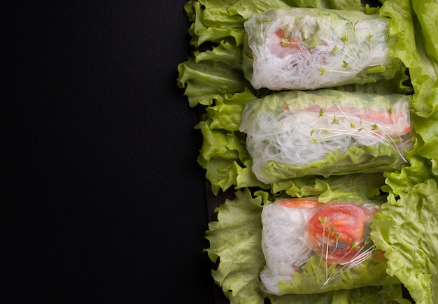 Vegetarian spring rolls with vegetables on black.
