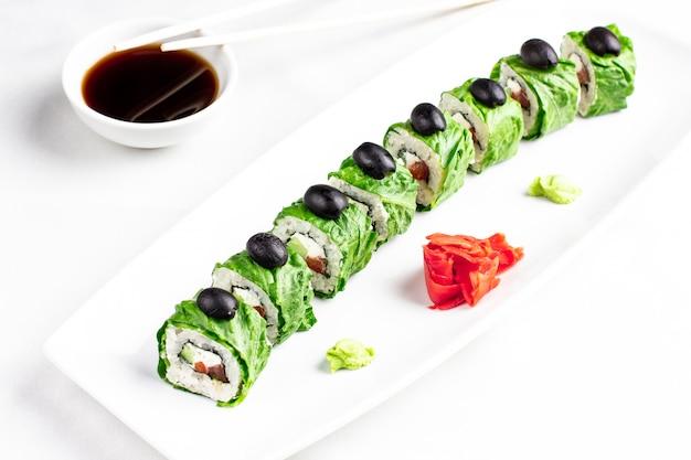 Vegetarian sushi rolls in lettuce leaves on white background