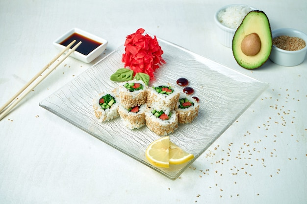 Vegetarian sushi rolls with vegetables and sesame seeds on a white plate in a composition with ingredients