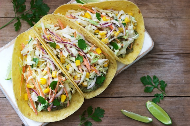 Vegetarian tacos stuffed with cabbage salad on wood
