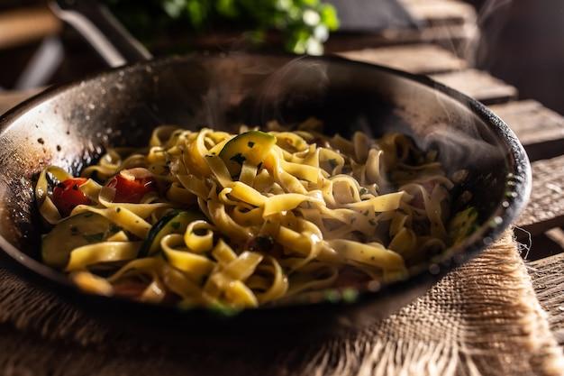 Вегетарианские тальятелле с кабачками и помидорами, подаваемые на раскаленной сковороде.
