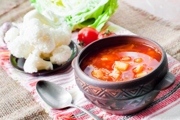 Vegetarian tomato soup with cabbage and cauliflower in a ceramic rustic bowl