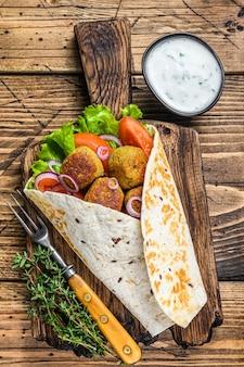 Vegetarian tortilla wrap with falafel and fresh salad, vegan tacos. wooden background. top view.