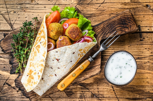 Vegetarian tortilla wrap with falafel and fresh salad, vegan tacos.