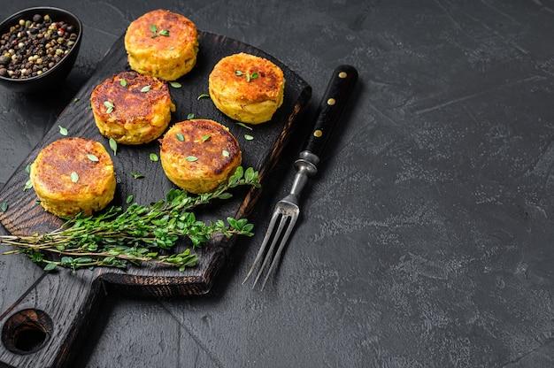 ベジタリアンビーガンバーガーのパテと野菜とハーブ。黒いテーブル。上面図。スペースをコピーします。
