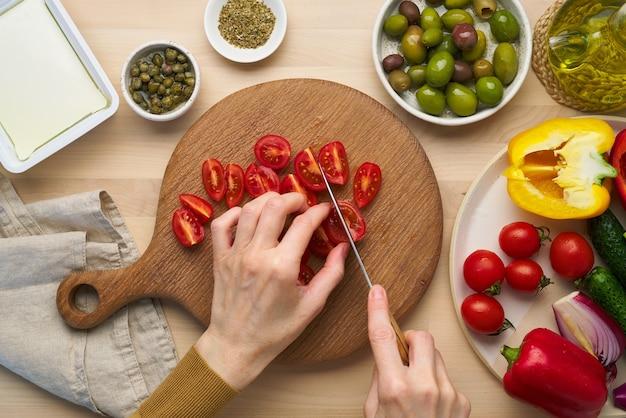 ベジタリアンビーガンフードトマトを刻んでギリシャ風サラダホリアティキの野菜を切る