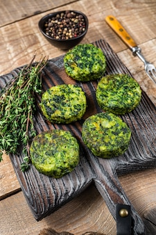 Vegetarian vegetable burgers patty with herbs on wooden board