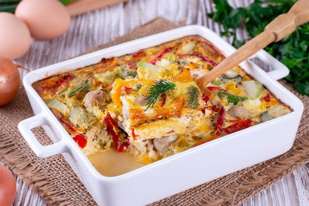 Вегетарианская овощная запеканка с цукини, стручковой фасолью, перцем, кукурузой на деревянном фоне
