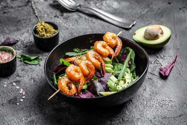 Вегетарианский обед с низким содержанием углеводов и овощами с авокадо, свежим салатом, креветками на гриле и соусом песто. концепция здорового питания. вид сверху.
