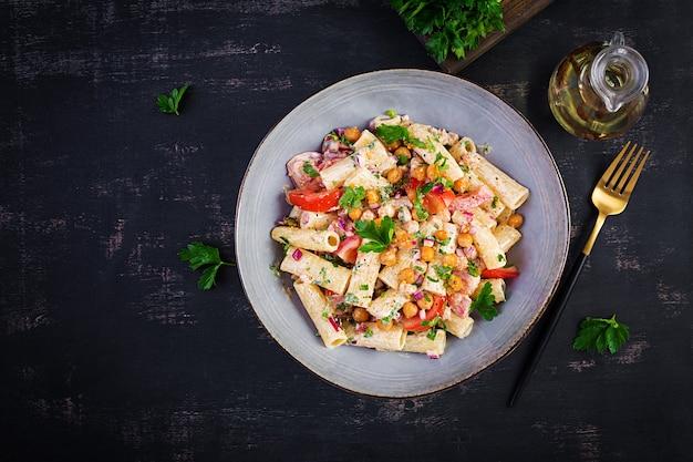 ベジタリアン野菜パスタ。トマト、赤玉ねぎ、パセリ、ひよこ豆のフライとナッツソースのパスタリガトーニ。ビーガンフード。上面図、オーバーヘッド