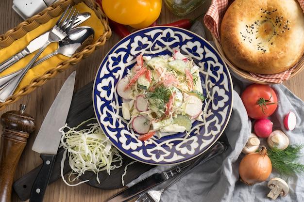 伝統的なウズベキスタンのプレートに大根とサワークリームのベジタリアン野菜サラダ