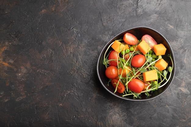 Вегетарианский овощной салат из помидоров, тыквы, ростков микрозеленого гороха на черном бетоне
