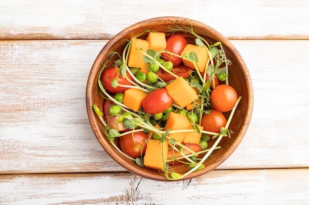 Вегетарианский овощной салат из помидоров, тыквы, проростков микрозелени на белом деревянном
