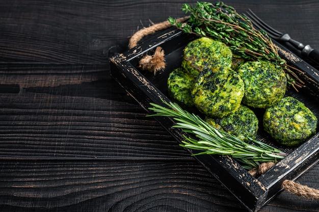 木製トレイにハーブとベジタリアン野菜野菜ファラフェルパティ。黒の背景。上面図。スペースをコピーします。