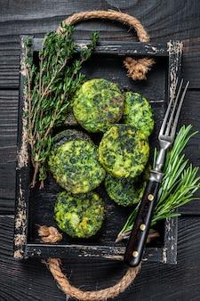 木製トレイにハーブとベジタリアン野菜野菜ファラフェルパティ。黒の背景。上面図。