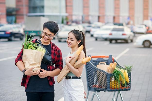 Вегетарианские вьетнамские пары держат бумажные сумки eco с органической здоровой едой в руках пока стоящ около торгового центра магазина. счастливая семья, покупки на выходные.