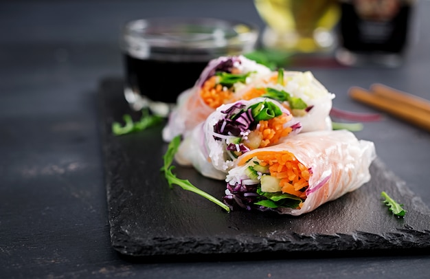 Vegetarian vietnamese spring rolls with spicy sauce, carrot, cucumber, red cabbage and rice noodle.