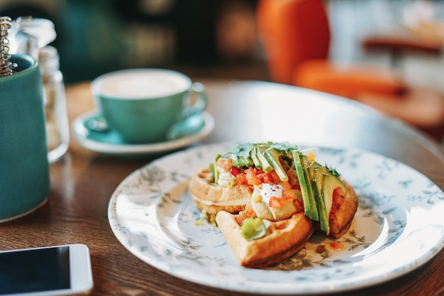 カフェのテーブルで新鮮な野菜とアボカドビジネスランチコーヒー携帯電話の白い画面とベジタリアンワッフル