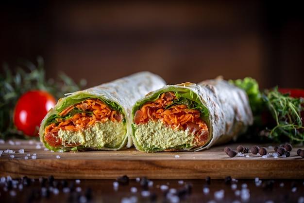 木製の背景に野菜ラップサンドイッチ