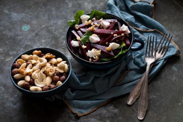 ほうれん草、山羊のチーズ、さまざまなナッツを使ったベジタリアンビートルートサラダ。ダイエット、健康、スナック、食事ランチのコンセプト。素朴な背景の上。