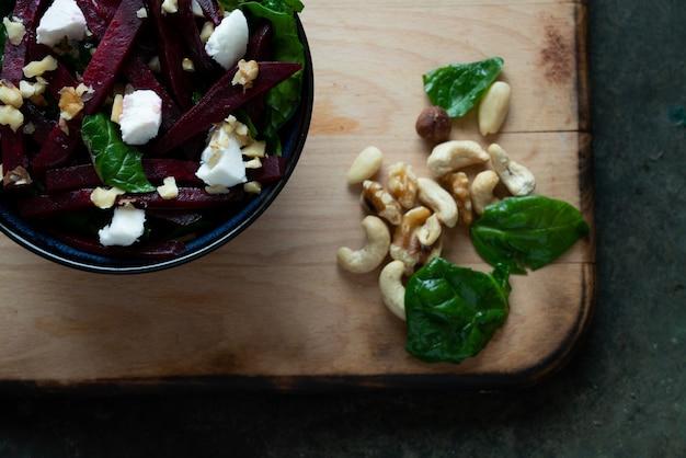ほうれん草、山羊のチーズ、さまざまなナッツをセラミックボウルに入れたベジタリアンビートルートサラダ。ダイエット、健康、スナック、食事ランチのコンセプト。素朴な背景の上。上面図。フラットレイ。