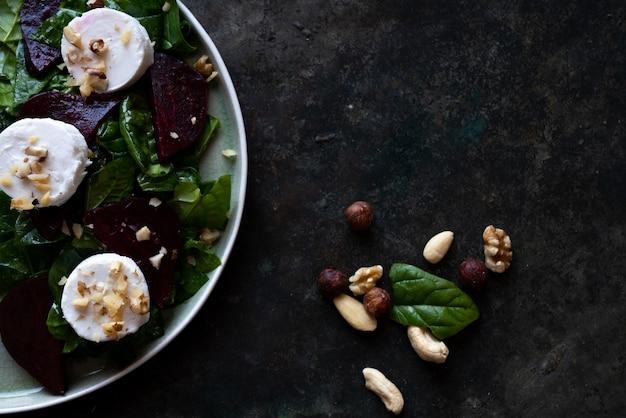 ほうれん草、山羊のチーズ、さまざまなナッツをセラミックプレートに載せたベジタリアンビートルートサラダ。ダイエット、健康、スナック、食事ランチのコンセプト。素朴な背景の上。上面図。フラットレイ